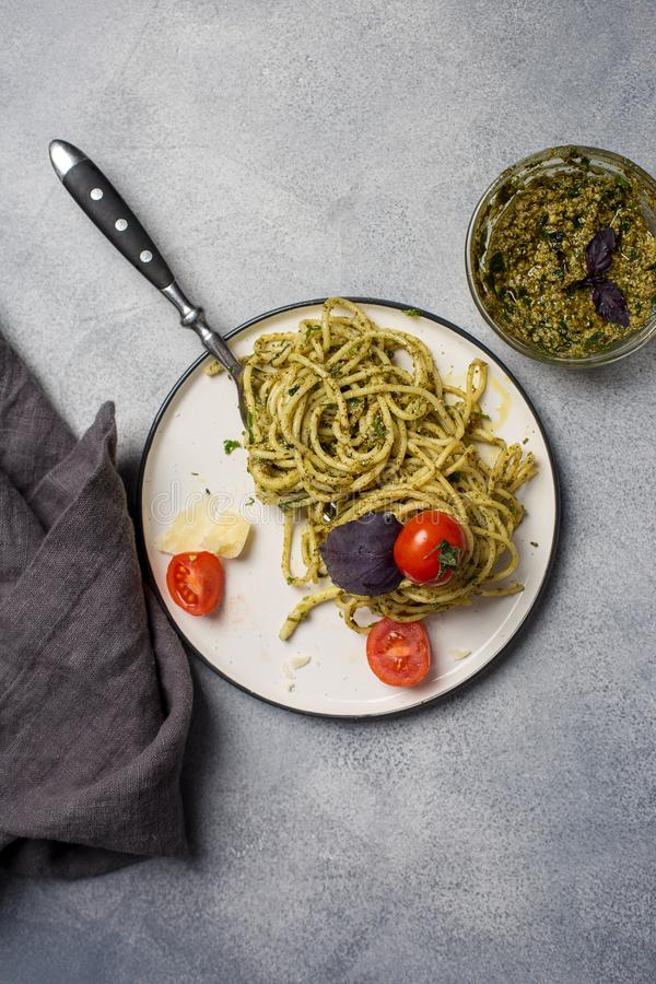 Pesto pasta with tomatoes and basil at white plate stock photo