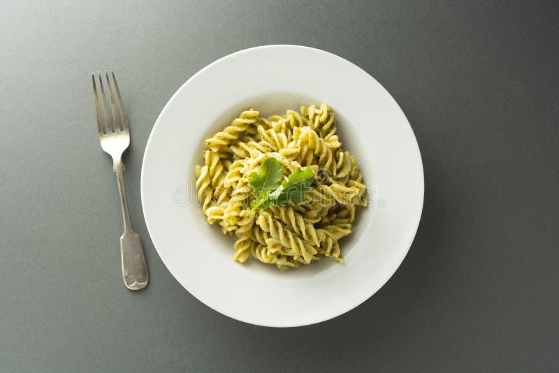 Pesto Pasta in white plate over gray background, fusili, spaghetti. Italian food stock image