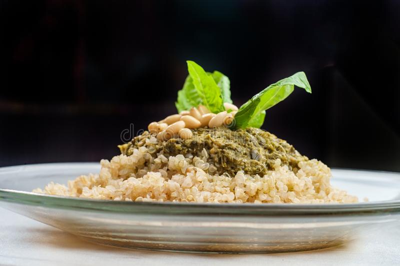 Pesto Quinoa Salad. Healthy pesto quinoa salad with basil and pine nut garnish royalty free stock images