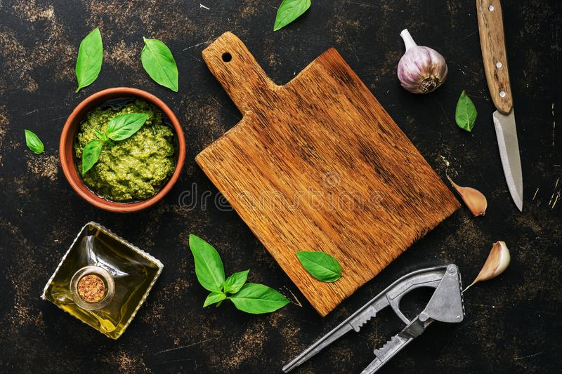 Pesto sauce, empty cutting board, basil leaves, garlic and olive oil on a dark rustic background. View from above stock image