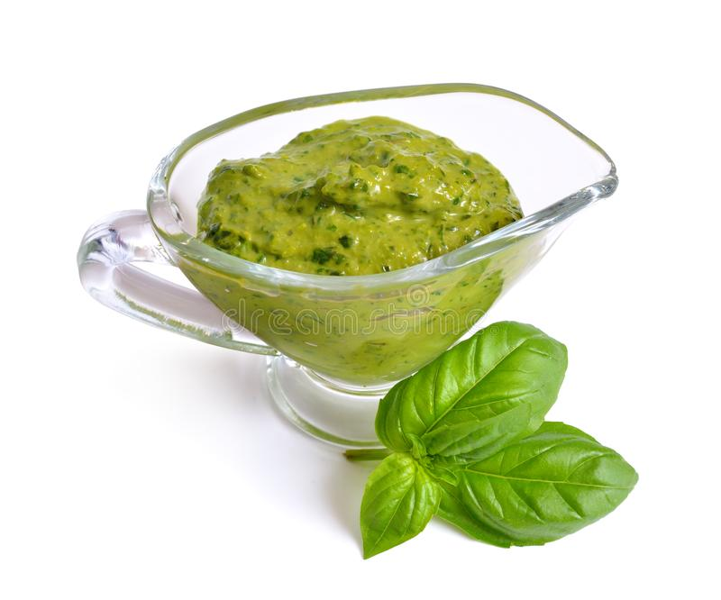 Pesto sauce in glass Sauce boat with basil leaf. Isolated. Pesto sauce in glass Sauce boat with basil leaf. Isolated stock photos