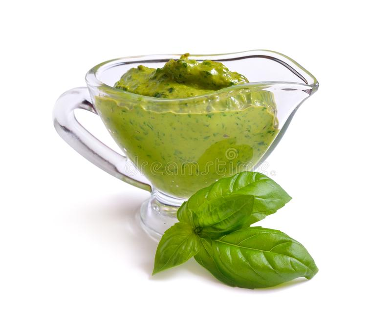 Pesto sauce in glass Sauce boat with basil leaf. Isolated. Pesto sauce in glass Sauce boat with basil leaf. Isolated stock image