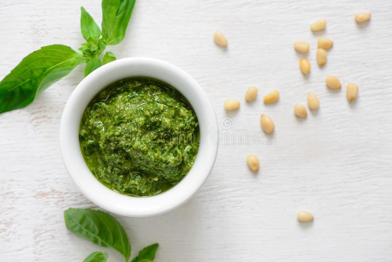 Pesto sauce, overhead view. Pesto sauce in a white bowl, view from above stock image