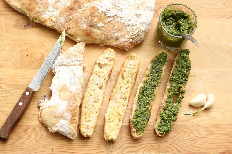 Pesto sauce, sliced roasted italian ciabatta bread for cooking bruschetta sandwiches stock images
