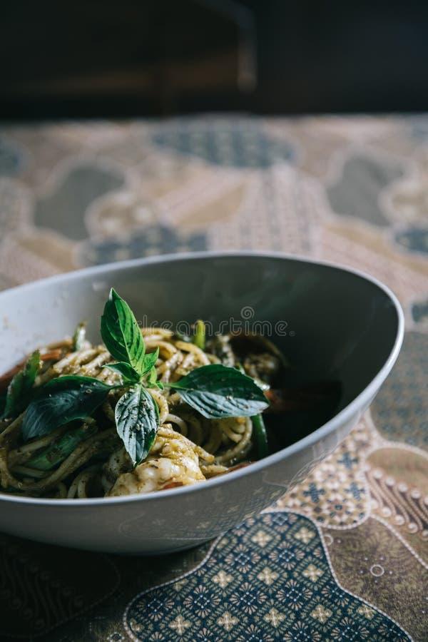 Pesto Spaghetti con chispas en alto contraste comida italiana imagen de archivo