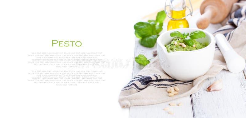 Pesto traditionnel fait maison de basilic avec l'huile d'olive, les écrous de cèdre et l'ail dans une cuvette blanche sur une tab photo libre de droits