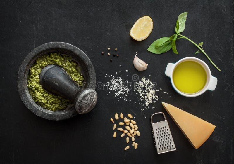 Pesto verde de la albahaca - ingredientes italianos de la receta en la pizarra negra foto de archivo libre de regalías