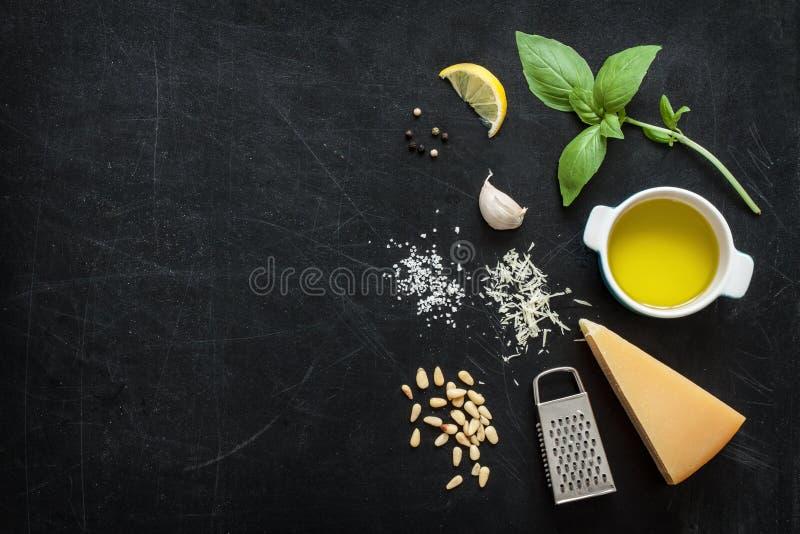 Pesto verde de la albahaca - ingredientes italianos de la receta en la pizarra negra imágenes de archivo libres de regalías