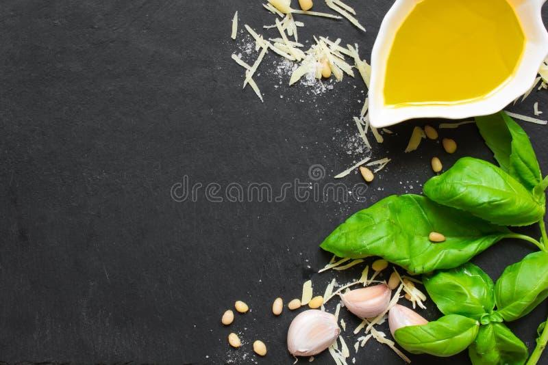 Pesto vert de basilic - ingrédients italiens de recette sur le fond noir de tableau image stock