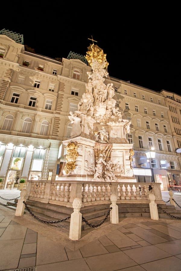 Pestsaule μεταξύ των φωτισμένων κτηρίων στη Βιέννη, Αυστρία στοκ εικόνα