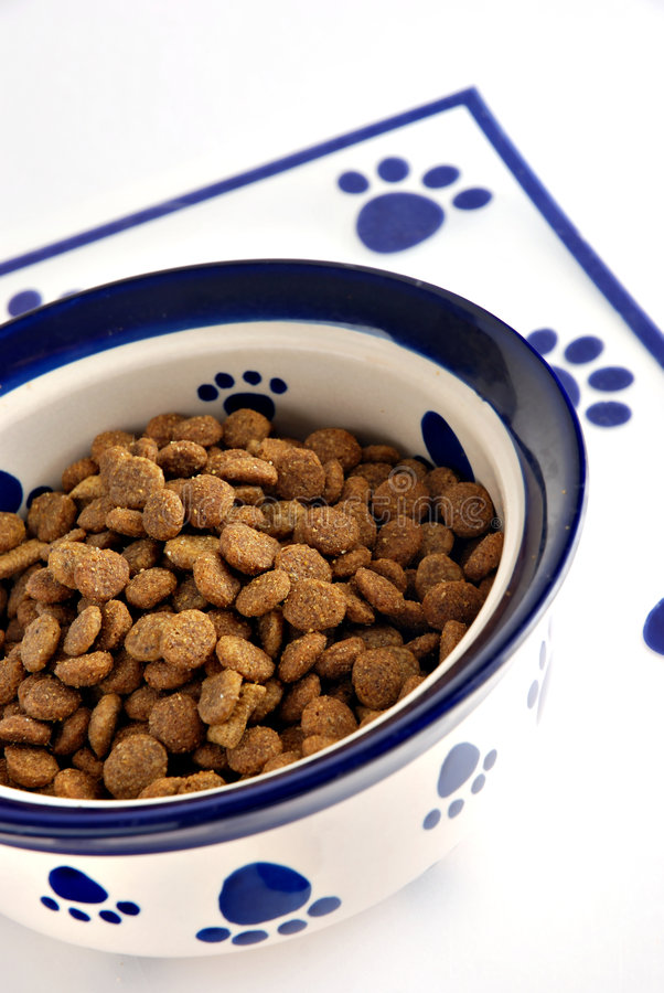 Pet food. Bowl of dry pet food and dog biscuits royalty free stock photos