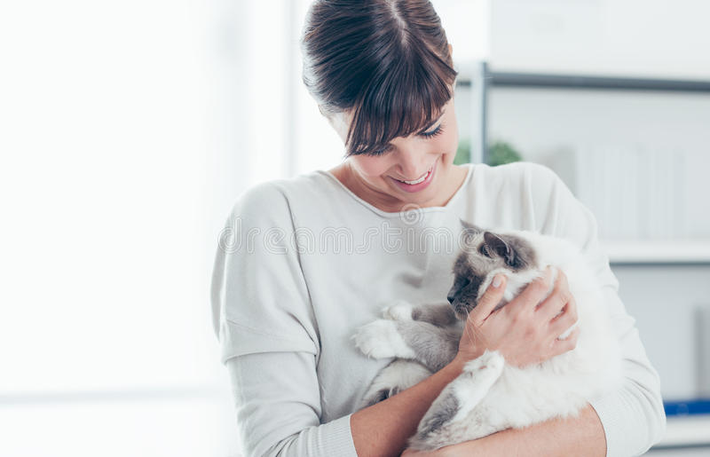 Pet owner with her cat. Young beautiful woman at home holding her lovely birman cat in her arms and cuddling it, pet care and lifestyle concept royalty free stock photography
