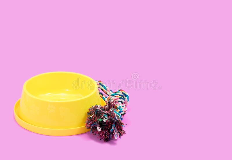 Pet supplies concept. Bowl with rope on pink background. stock image