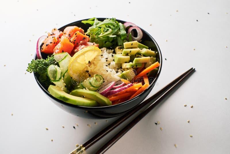 peta bunken med laxen, avokadot, gurkan, arugula, broccoli, ris, moroten och söta lökar med pinnar som isoleras över vit royaltyfri bild
