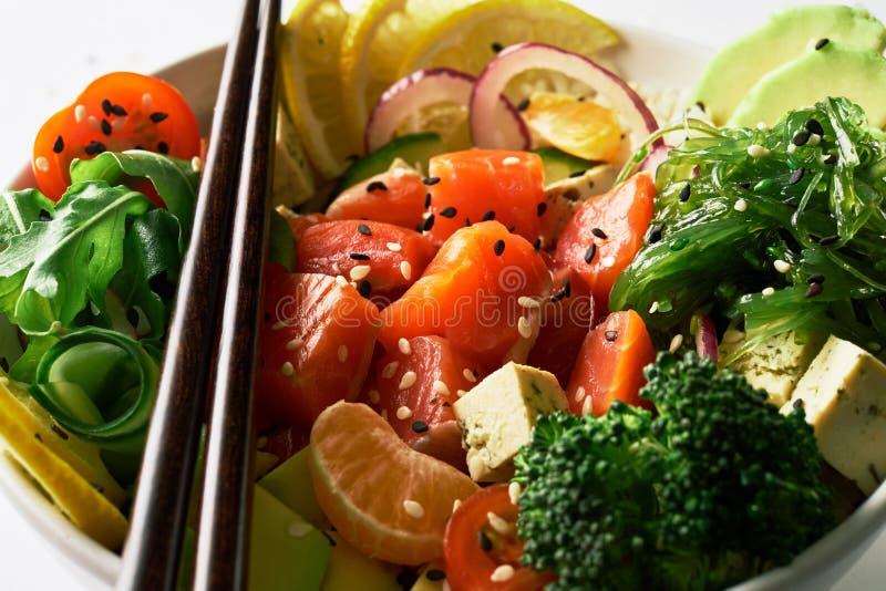 peta bunken med laxen, avokadot, gurkor, arugula, broccoli, ris, morötter, ost och chukha med pinnar över vit arkivbilder