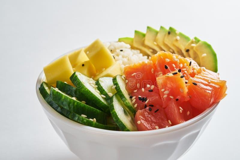 peta bunken med laxen, avokadot, mango, ris, gurkor som strilas med vit och svart sesam som isoleras på vit bakgrund Close- arkivbild