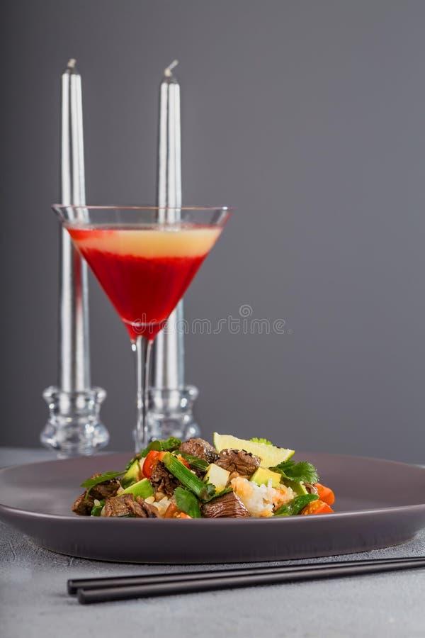 Peta med nötkött och ris på en härlig platta med stearinljus och ett exponeringsglas av drinken Hawaiansk kokkonst royaltyfria bilder