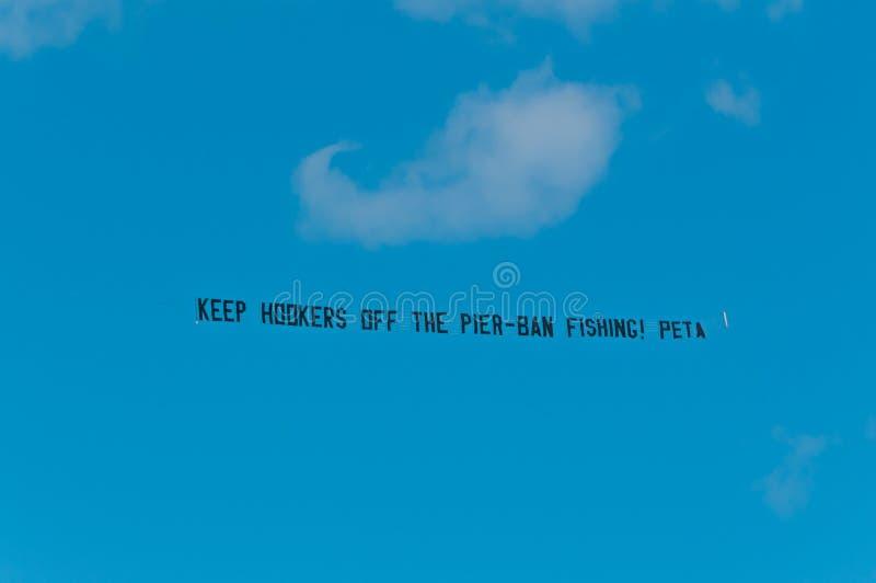 PETA-Protest-Flugzeugflagge gegen Fischen eines Piers lizenzfreie stockfotos