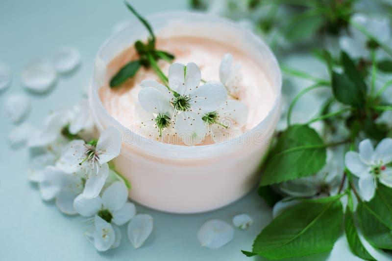 Petali della crema per il corpo e del fiore immagini stock libere da diritti