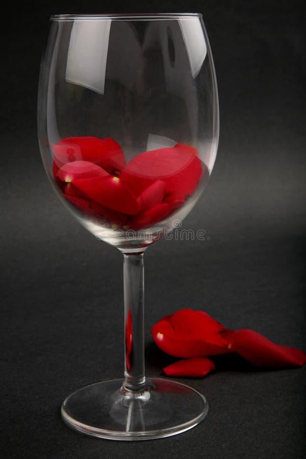 Petali di Rosa in un vetro di vino fotografie stock libere da diritti