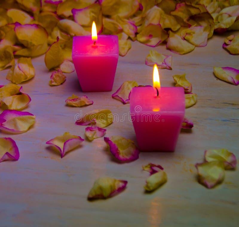 Petali e candele rosa brucianti su fondo di legno immagini stock