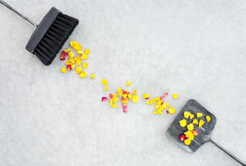 Petali rosa, spazzola e paletta per la spazzatura gialli sul pavimento di calcestruzzo immagine stock