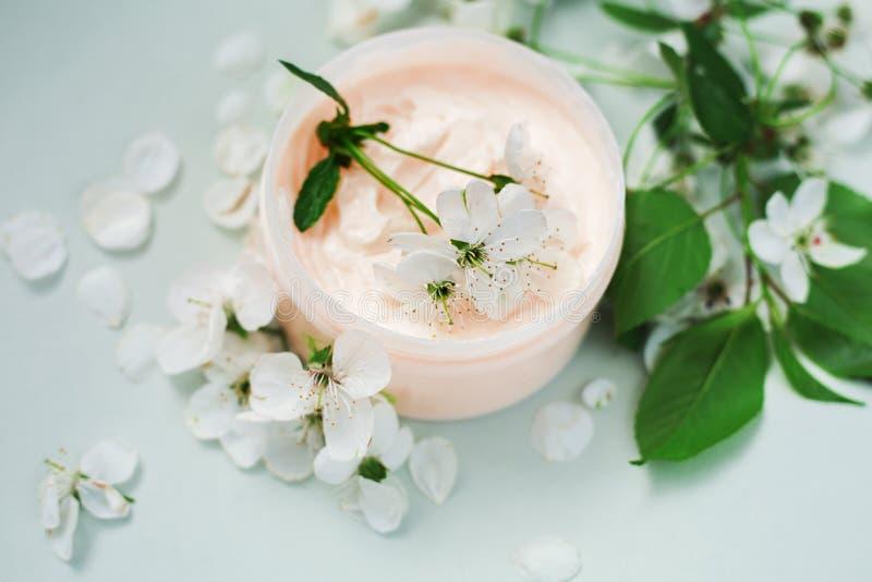Petalo e un barattolo della crema per il corpo naturale immagine stock