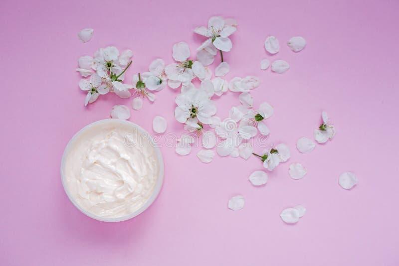Petalo e un barattolo della crema per il corpo naturale fotografia stock