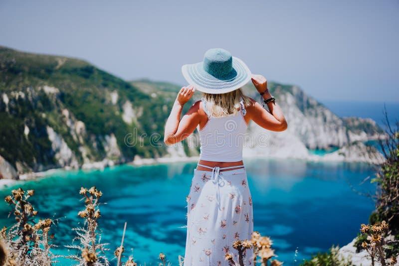 Petani海滩的Kefalonia少妇,拿着蓝色sunhat享受鲜绿色天蓝色的海湾盐水湖的美丽如画的全景  免版税库存照片