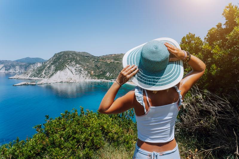 Petani strand Kefalonia För innehavblått för ung kvinna som hatt för sol tycker om härlig panorama av blåttfjärdlagun som förbi o arkivfoto