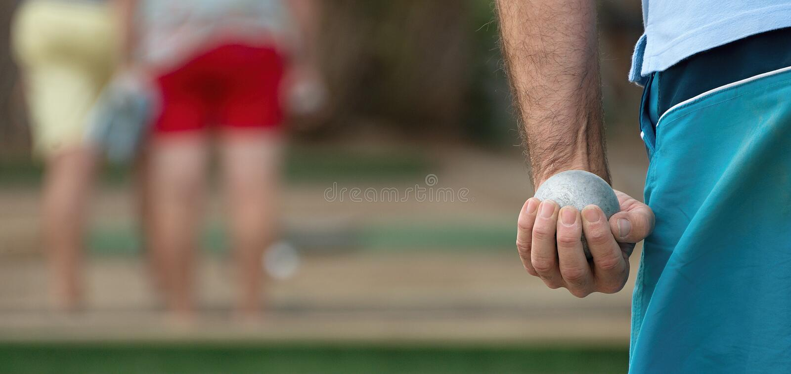 Petanque ball in hand of man. Senior playing petanque,fun and relaxing game.Petanque ball in hand of man royalty free stock photo