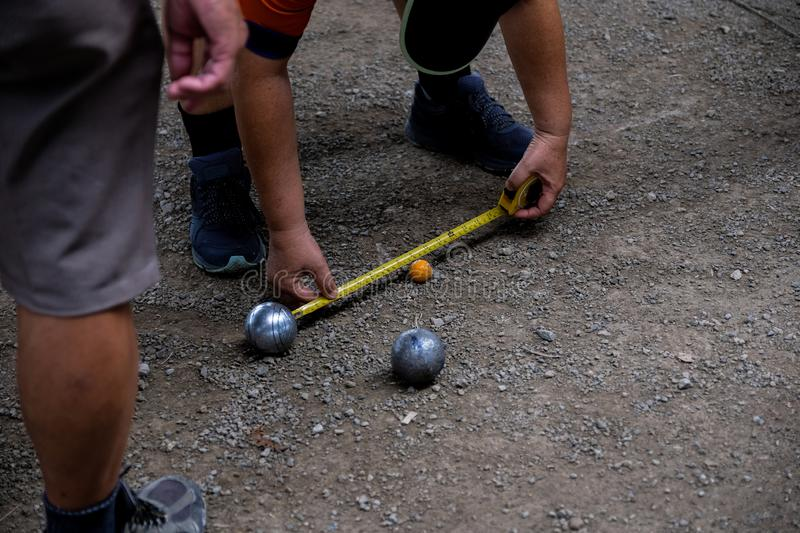 Petanque game, man measuring the distance of petanque ball in petanque field royalty free stock photos