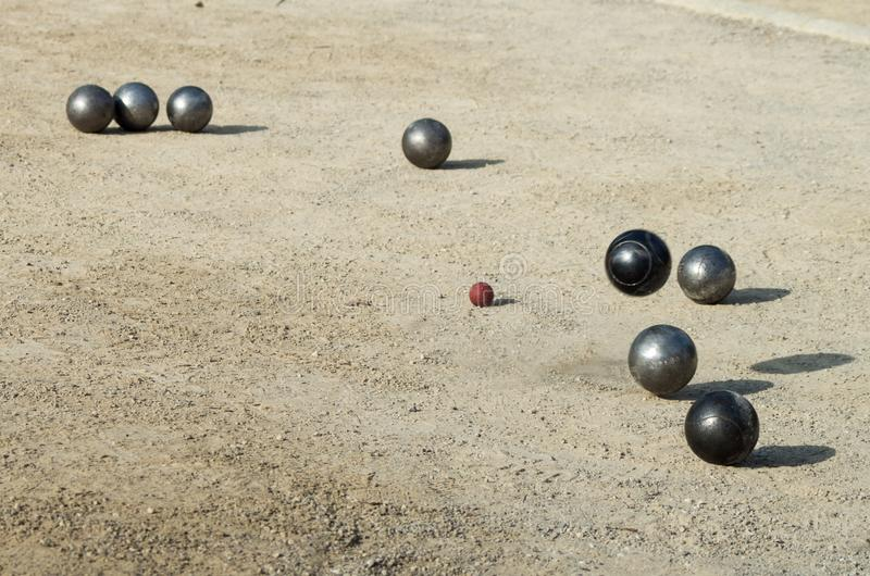 Petanque, game and sport with iron balls colliding with each other. Eight iron balls, colliding with each other, on dirt floor, raising dust stock photo