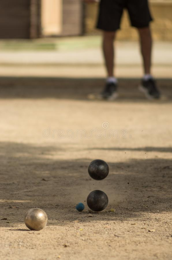 Petanque, game and sport with iron balls colliding with each other. A rope with Four iron balls, colliding with each other, on dirt floor, raising dust. At the stock images