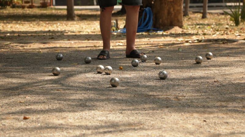 Petanque im Park - Metallbälle und orange hölzernen Ball auf Rock-Yard mit einem Mann spielen, der im Sun steht lizenzfreies stockbild