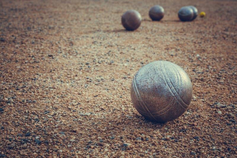 Petanqueballen op een zandige hoogte met andere metaalbal stock fotografie