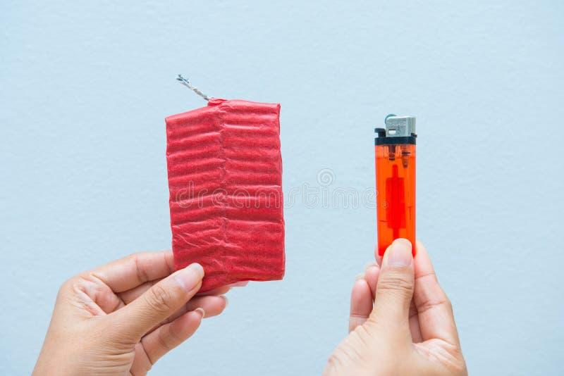 Petardos rojos y un encendedor a disposición foto de archivo libre de regalías
