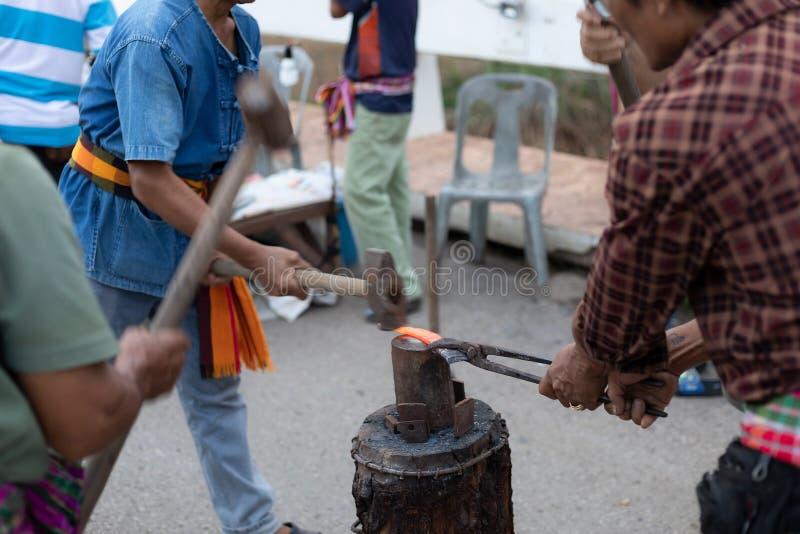 Petchaboon prowincja, Thailand-30 Czerwiec, 2018 - Metalworkers przedstawienia szlagierowy gorący żelazo dla noża na chodzącym ul obrazy stock