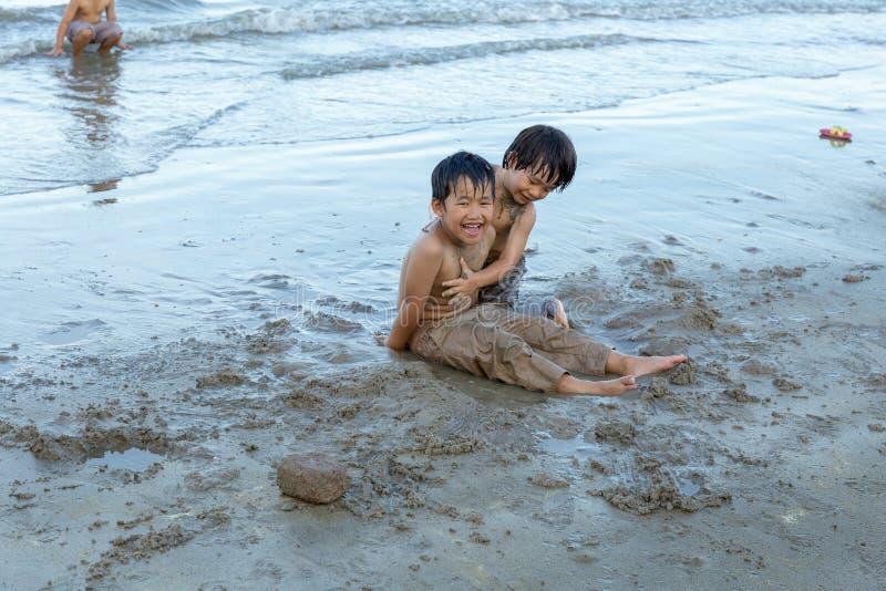 Petchaburi/泰国- 2018年5月9日:使用在沙子和波浪的年轻男孩在海滩 库存图片
