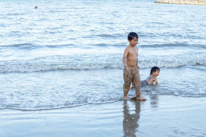 Petchaburi/Tailandia - 9 maggio 2018: Giovane ragazzo che gioca nella sabbia e nelle onde sulla spiaggia fotografie stock