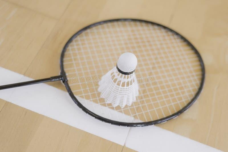 Peteca branca do badminton em um assoalho do salão em cortes de badminton Feche acima das petecas no badminton da raquete em cort fotografia de stock royalty free