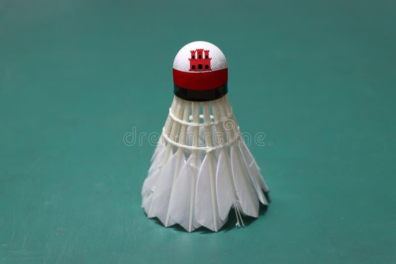 A peteca usada e na cabeça pintada com bandeira de Gibraltar pôs vertical sobre o assoalho verde da corte de badminton imagem de stock royalty free