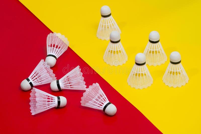 Petecas e raquete do badminton contra uma parte traseira vermelha e amarela fotografia de stock