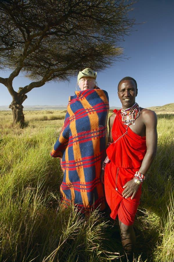 Peter Bender na veste superior da pessoa idosa e no guerreiro do Masai que estão a árvore próxima da acácia na tutela de Lewa de  imagens de stock