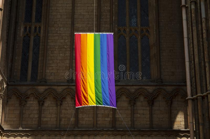 Peterborough, Cambridgeshire, UK, July 2019, A view of a Pride flag hanging from Peterborough Cathedral. Peterborough, Cambridgeshire, United Kingdom, July 2019 royalty free stock photos