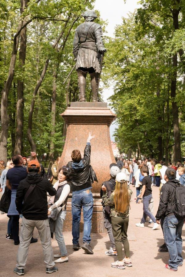 Petergof Ryssland, Juli 2019 Besökare till parkerar kastmynt för blasten av kängorna av statyn av Peter royaltyfria bilder