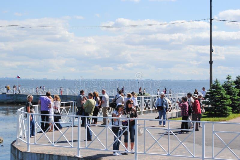 PETERHOF, RUSIA - 1 DE JULIO DE 2011: Los turistas que navegaron a Petergof en la nave están en el embarcadero foto de archivo