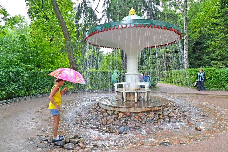PETERHOF, RUSSIA. The girl about the Umbrella fountain cracker in Nizhny park royalty free stock photography