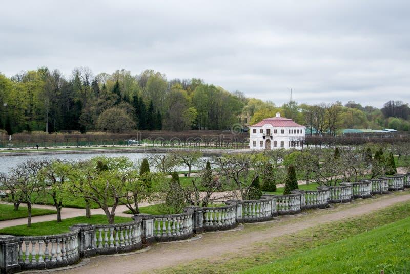 PETERHOF, RUSSIA - 10 MAGGIO 2015: Abbassi i giardini del parco di Peterhof, una vista ad uno stagno e ad una casa sola immagini stock libere da diritti