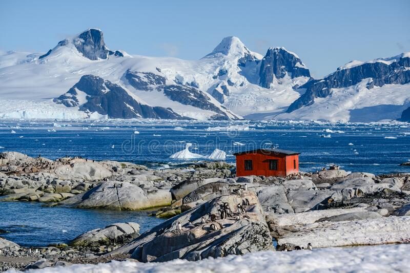 Petermann Island, beautiful Antarctic Island with penguins on rocks, abandoned station and snow covered mountains behind Ocean. royalty free stock images